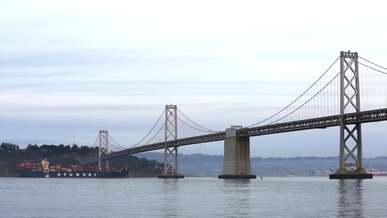 Ship And Yacht Passing Under Suspension Bridge