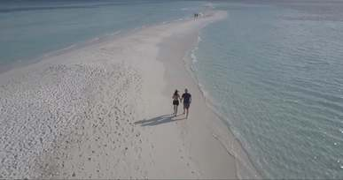 Couple Walking on a Beach Filmed with a Drone