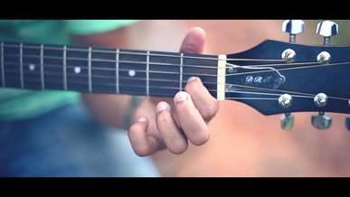 Man Wearing Green Shirt Playing with a Guitar